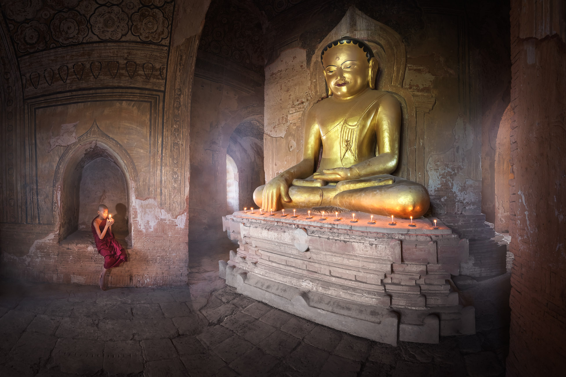 Monk Praying Inside Ancient Temple with the Seated Golden Buddha, Bagan, Myanmar