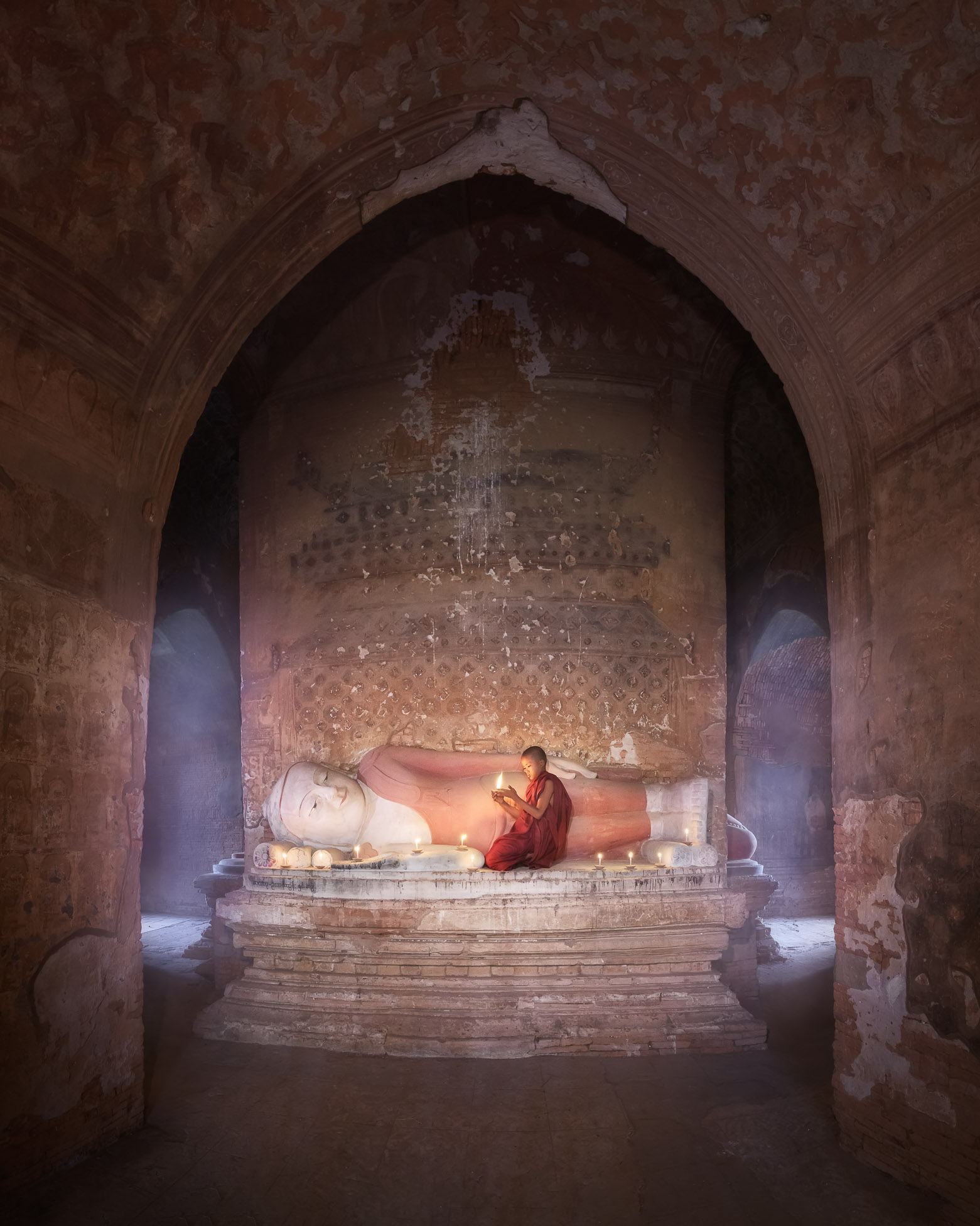 Monk Praying Inside Ancient Temple with the Reclining Buddha, Bagan, Myanmar